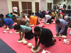 Participants practice CPR on inflatable mannequins during the first session on the CPR training.